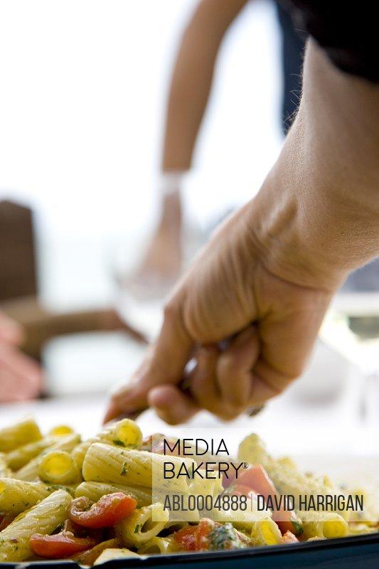 Close up of a man hand serving rigatoni pasta