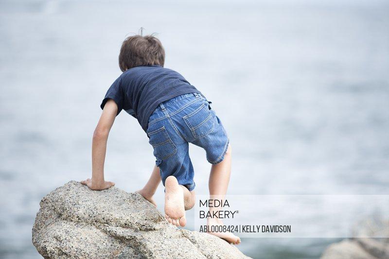 Boy Climbing Rock by Sea