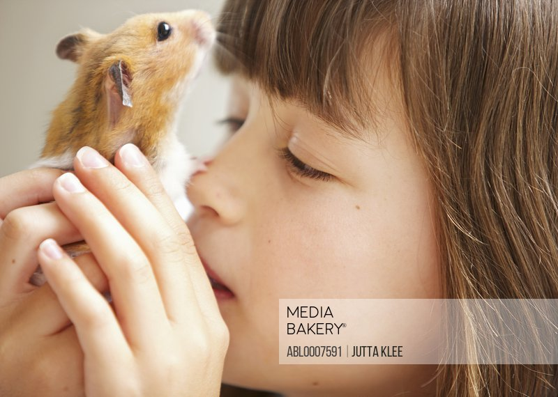 Girl Holding Hamster in front of Face