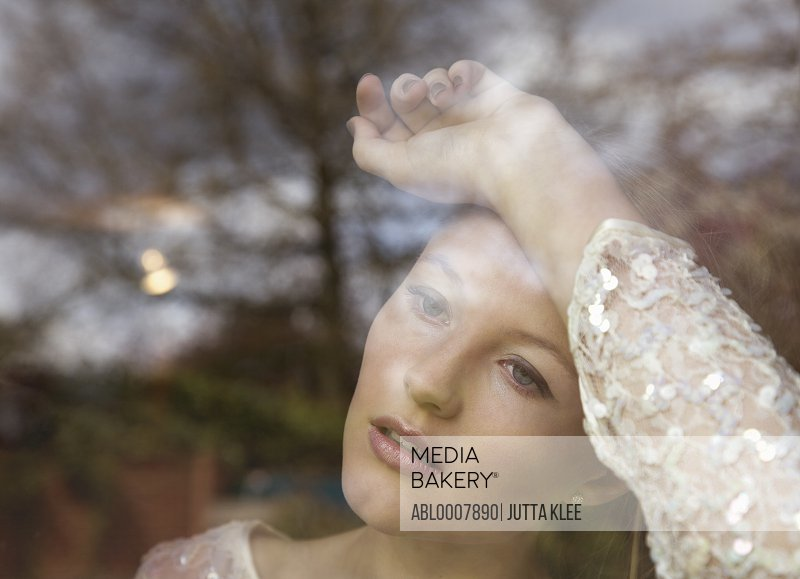 Young Woman Behind Window Pane