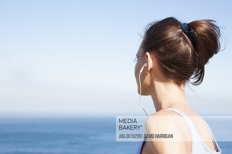 Back View of Woman Wearing Earbuds Looking at the Ocean