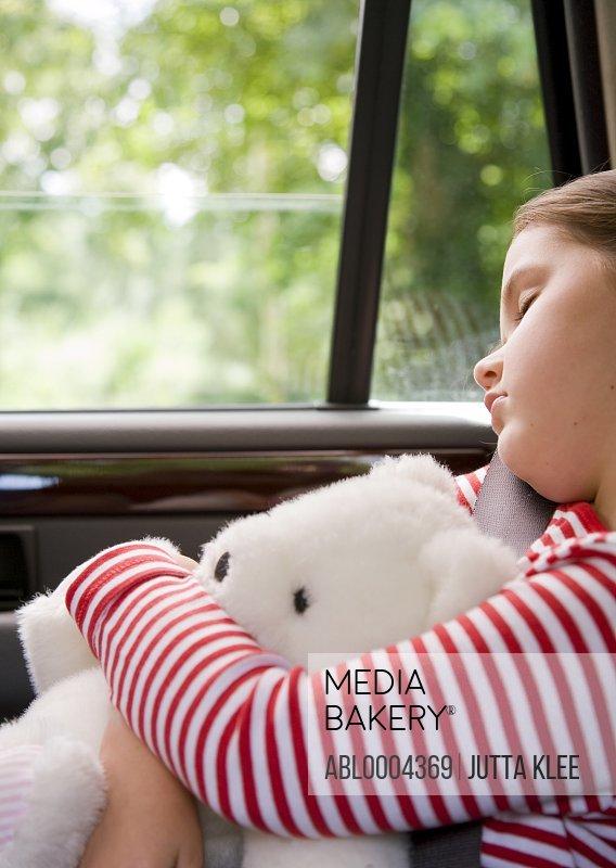 Portrait of a girl sleeping and cuddling teddy bear