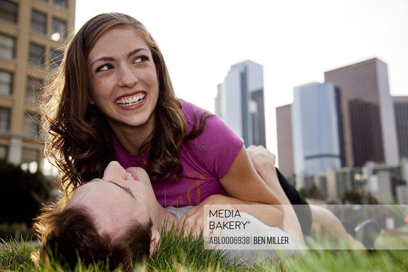 Couple Lying on Grass Hugging