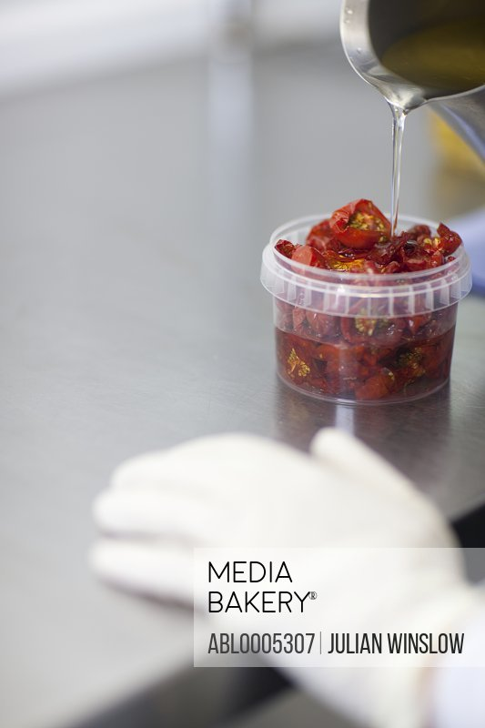 Close up of a worker hand pouring oil in a plastic container filled with sun dried tomatoes