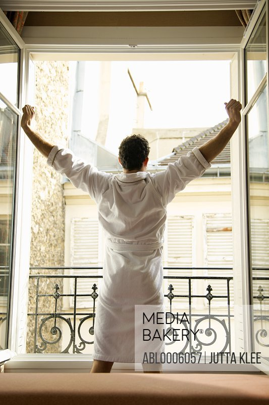Back view of a man stretching his arms in front of an open window