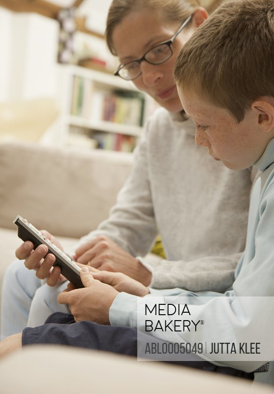 Woman sitting next to young boy holding a remote control