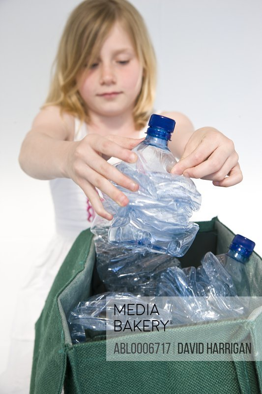 Young Girl Recycling Plastic Water Bottles