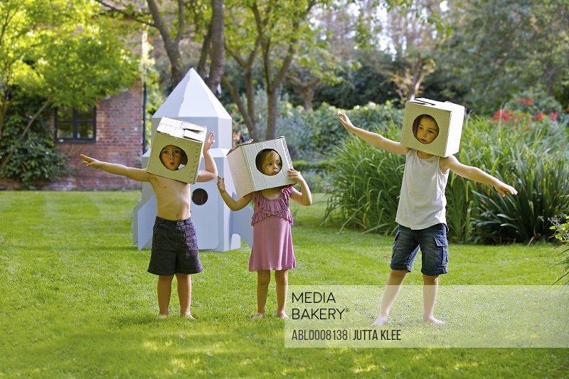 Children Wearing Homemade Cardboard Helmets Playing around Rocket Spacecraft