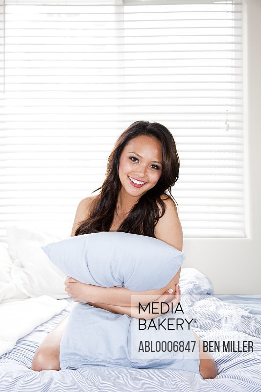 Young Woman Kneeling on Bed Hugging Pillow