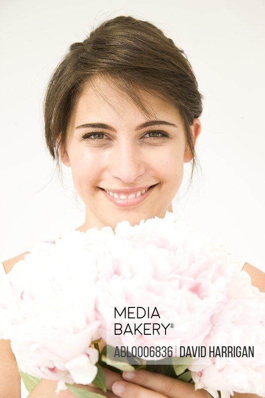 Smiling Woman Holding Pink Peonies