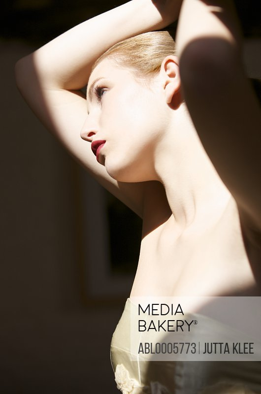 Young woman standing in shadowed lighting wearing a gold dress