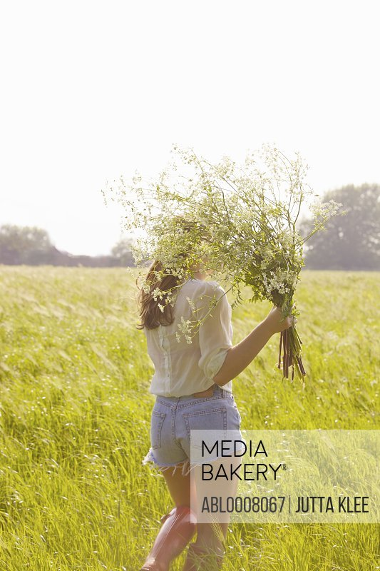 Back View of Young Woman in a Field Holding a Bunch of Wildflowers