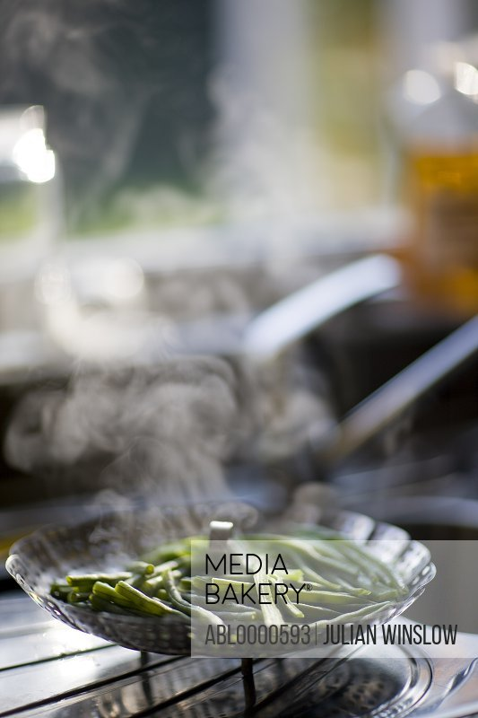 Green beans steaming in a stainless steel steamer