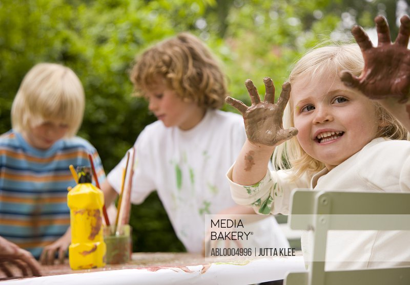 Young girl sitting at table holding arms up with hands covered in paint