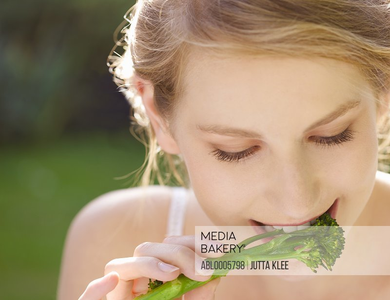 Close up of a young woman eating broccoli
