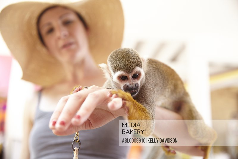 Woman Holding Spider Monkey on her Arm