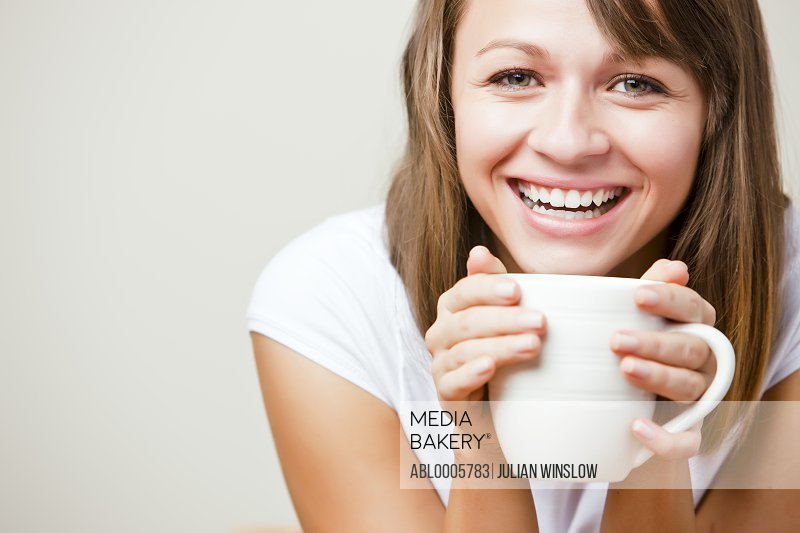 Smiling young woman holding a mug