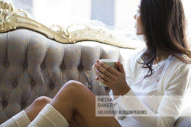Woman Sitting on Sofa Having Hot Drink