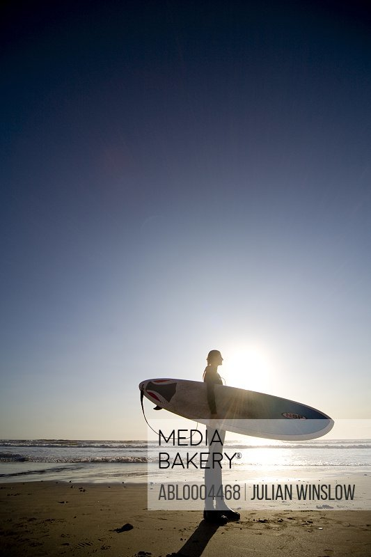 Young woman surfer standing on a beach with surfboard