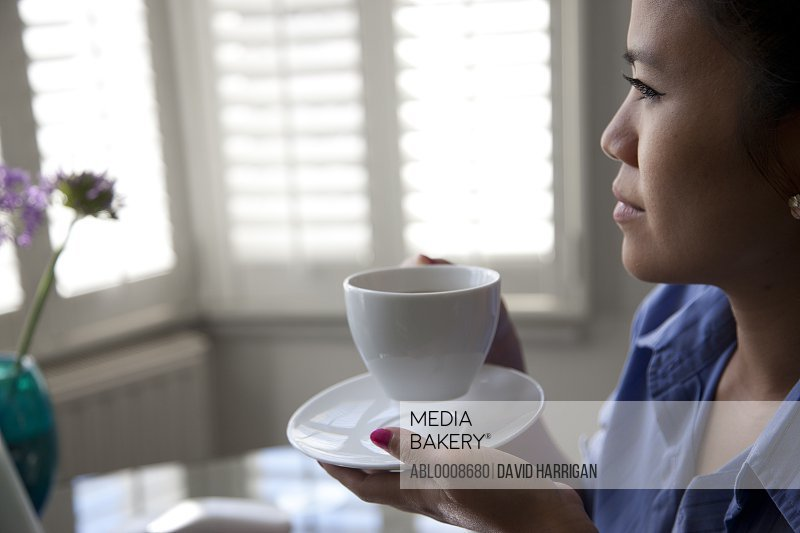 Woman Sitting at Desk Having Coffee