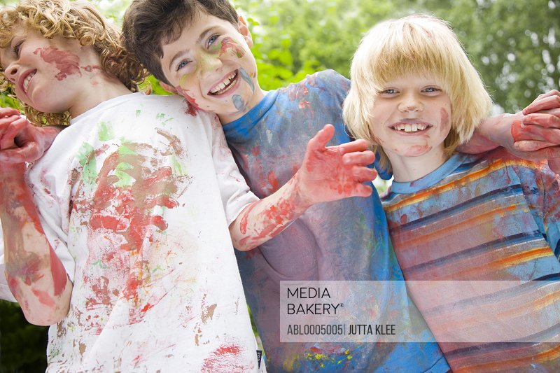 Young boys covered in watercolor paint laughing in a garden