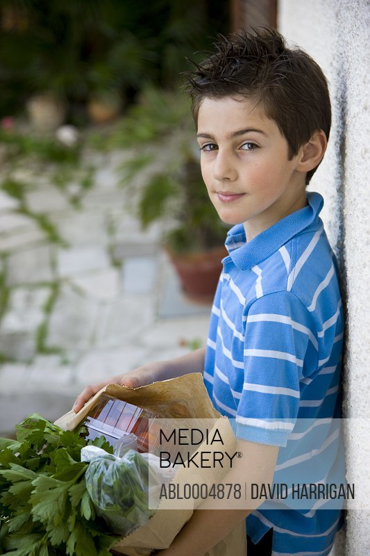 Young boy holding a brown paper bag full of fruit and vegetables