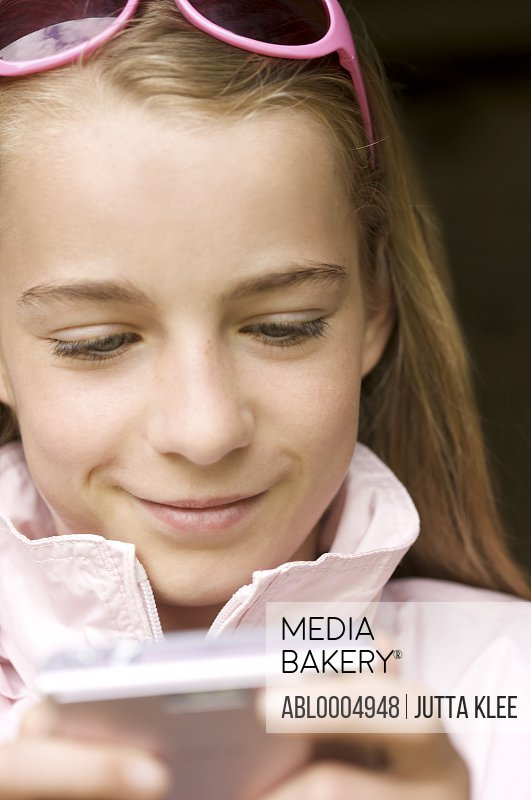 Close up of a girl smiling and holding a digital camera