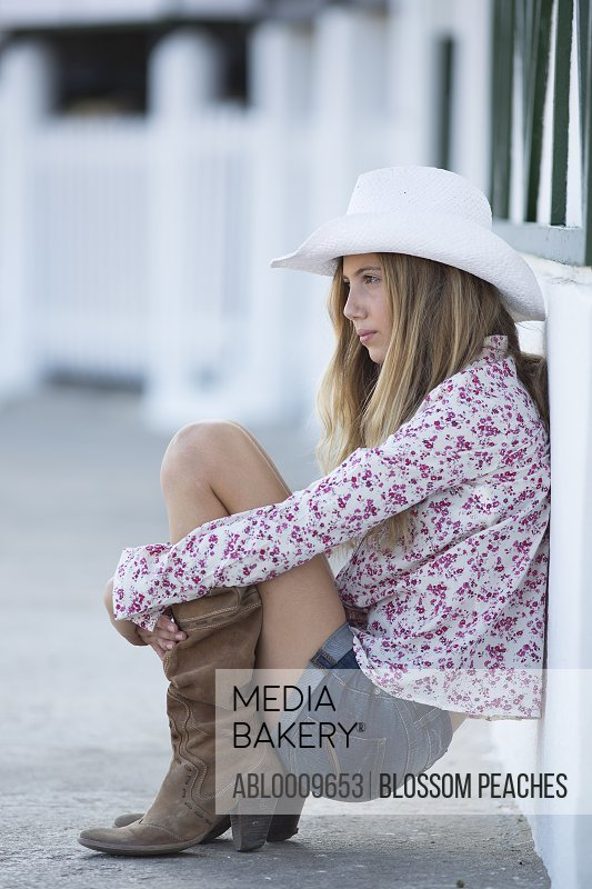 Teenage Girl Wearing Cowboy Hat Crouching against Exterior Wall, Side View