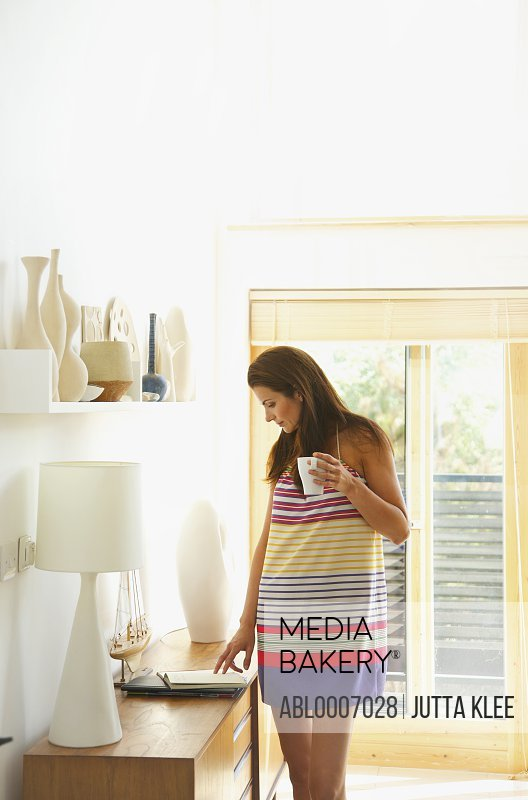 Woman Checking Diary whilst Holding a Coffee Mug