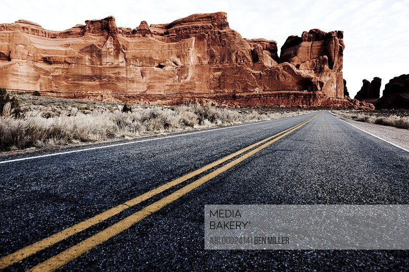 Double Yellow Line on Highway and Sandstone Formations