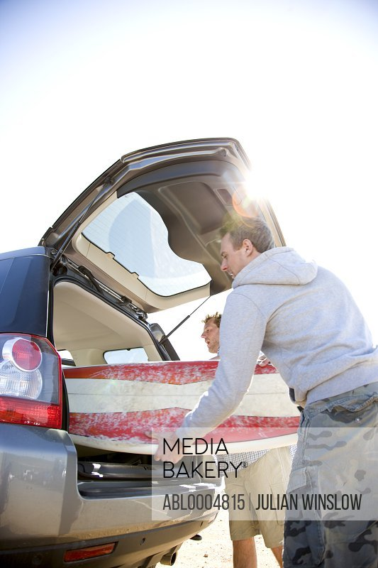 Two young men unloading surfboards from car boot