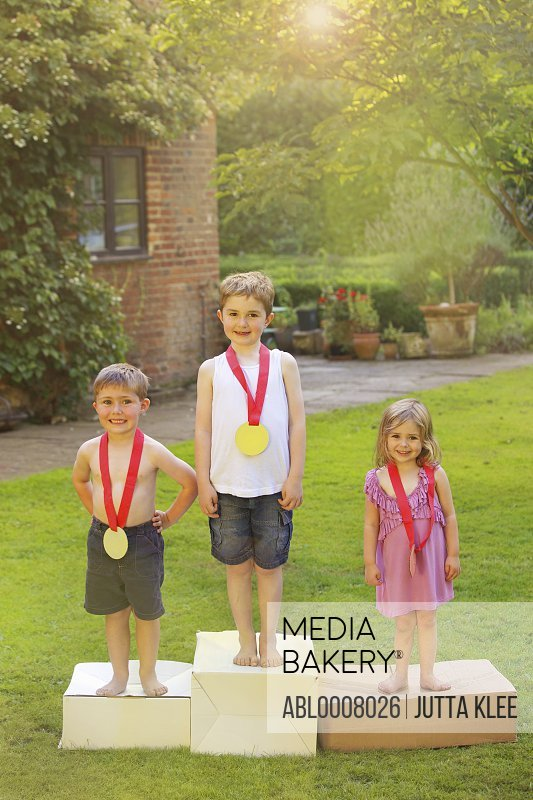 Children Standing on Cardboard Podium with Medals