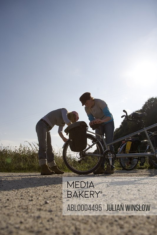 Two women checking tandem bicycle wheel in country road