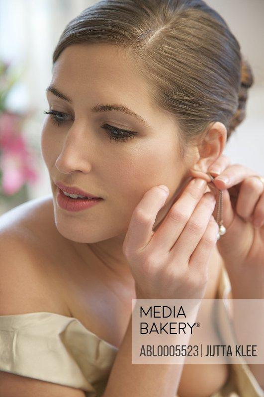 Bride adjusting her earrings