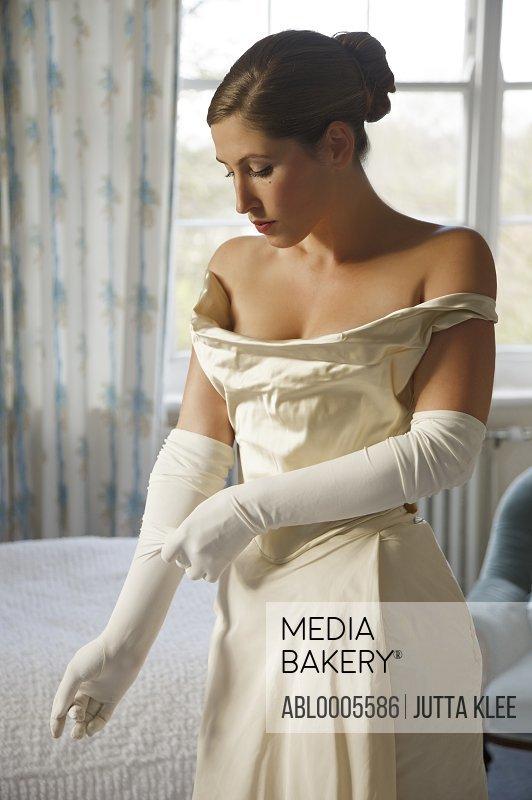Bride in white wedding gown adjusting her glove