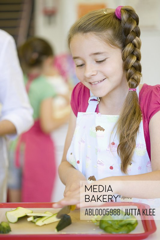 Young girl in cookery class cutting vegetables