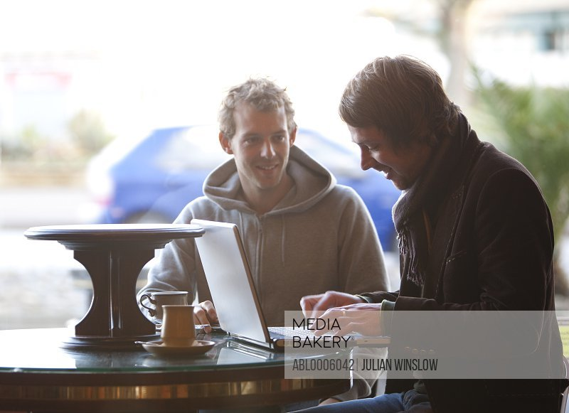 Two men using a laptop in a cafe