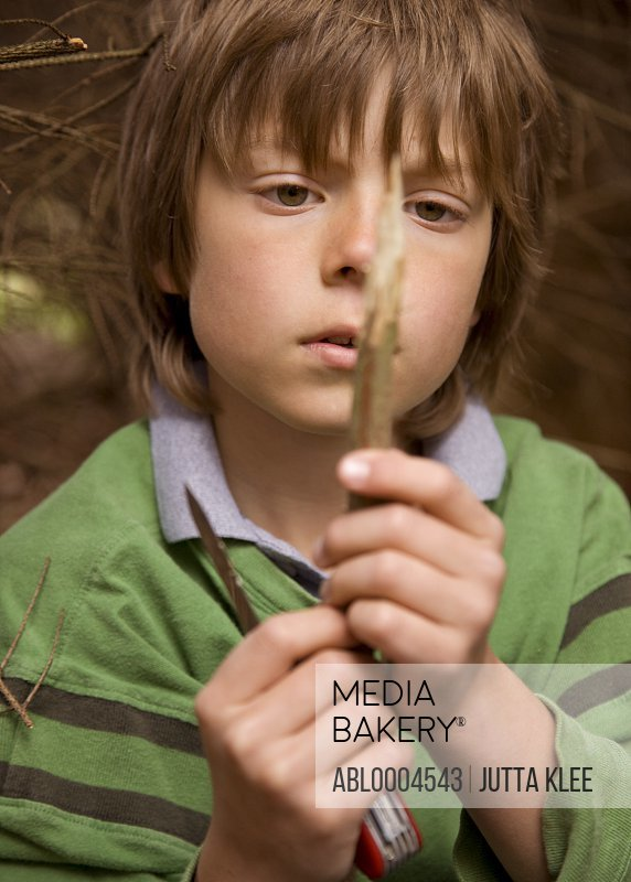 Close up of boy sharpening a wooden stick in a campsite