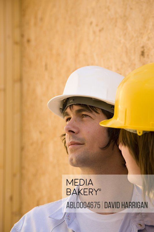 Close up of man wearing hard hat standing next to woman at construction site