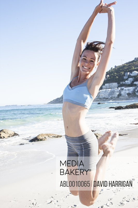 Woman Jumping Mid-air on Beach Smiling