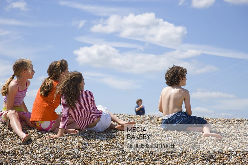 Children sitting on a beach watching a  young boy flying a kite