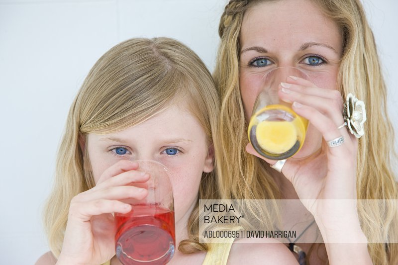 Woman and Young Girl Drinking Juice