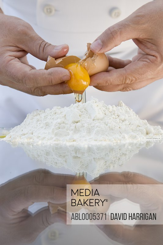 Close up of a chef hands breaking an egg above a heap of flour over a glass table