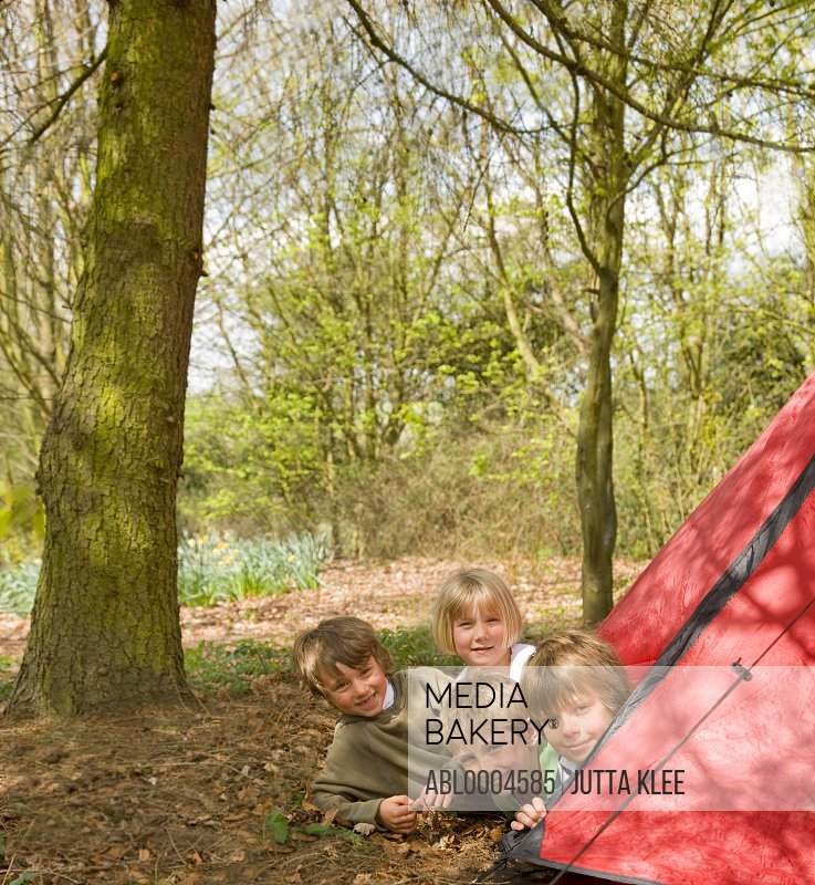Portrait of children coming out of tent opening