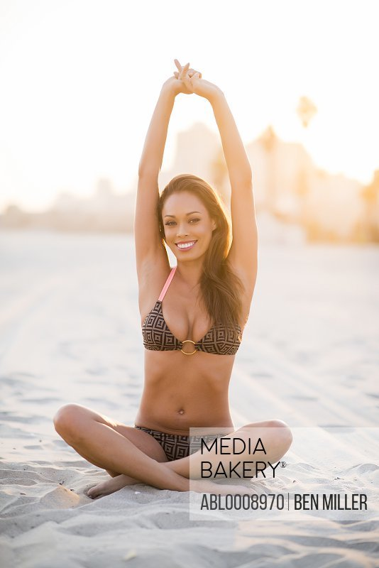 Smiling Woman on Beach Stretching Arms