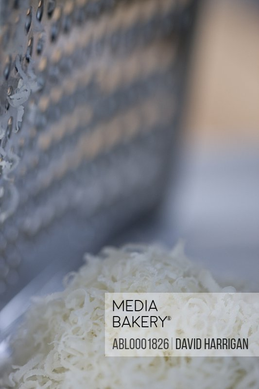 Close up of a cheese grater and parmesan cheese