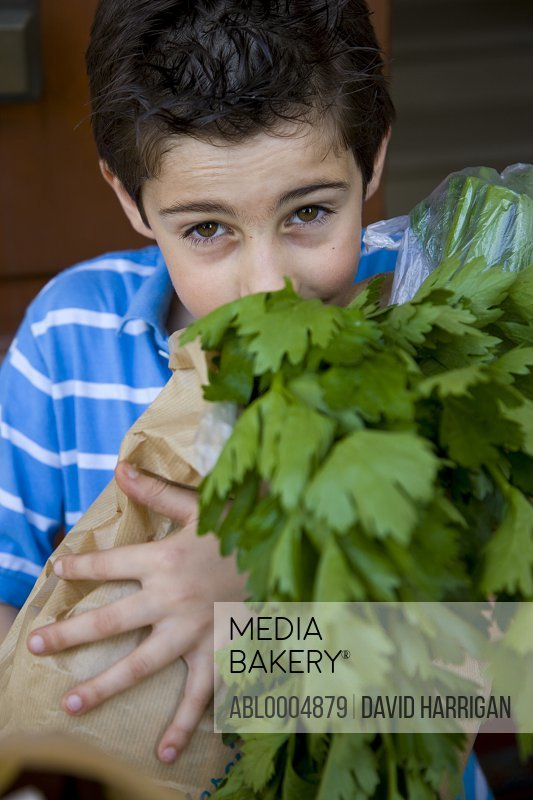 Close up of a young boy holding a brown paper bag with celery leaves