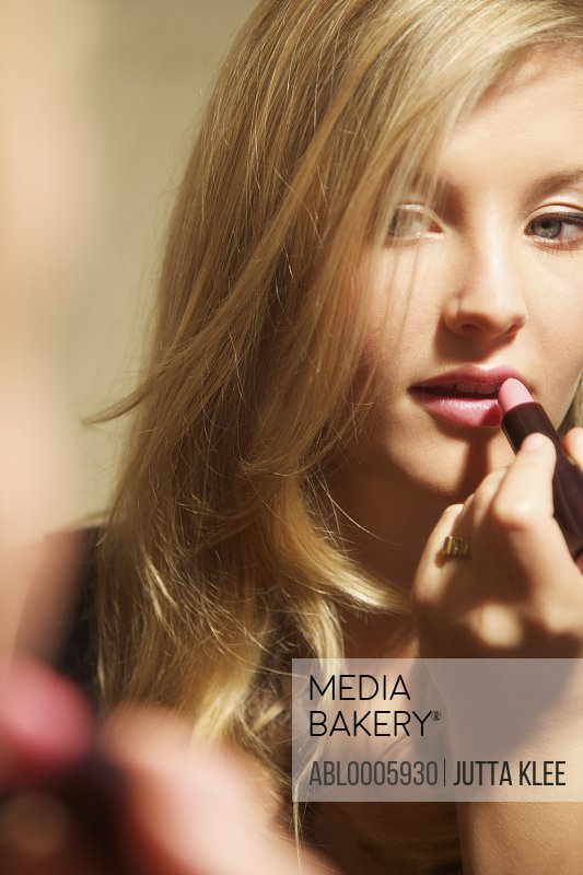 Close up of a young woman applying lipstick in front of a mirror