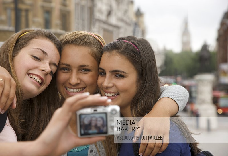 Three smiling teenaged girls taking a self-portrait with digital camera in London, England