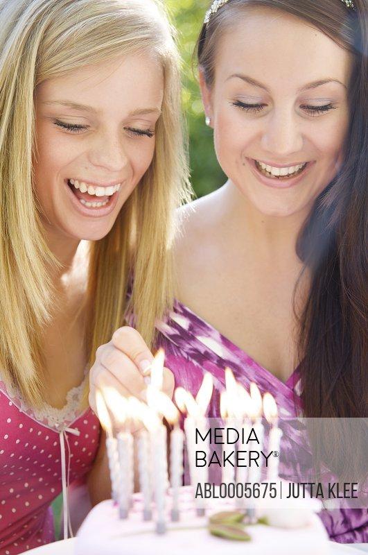 Girls lighting candles on a birthday cake